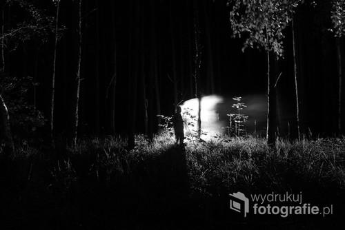 Jedno z moich ulubionych zdjęć, jestem z nim związany w pewien sposób emocjonalnie. Przedstawia postać na tle lasu, oświetloną przez latarkę.