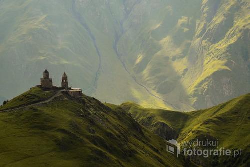 Zdjęcie zostało wykonane podczas podróży do północnej części Gruzji.  Przedstawia XIV wieczny, prawosławny klasztor Cminda Sameba, położony na wysokości 2170 m n.p.m, nad którym znajduje się szczyt góry Kazbek, jendej z najwyższych Kazukazu. Pod klasztorem znajduje się mała wioska Gergeti.