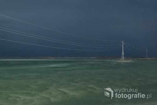 Burza nadciągająca nad Morze Martwe  w izraelu, z jednej strony pełne słońce, z drugiej mroczne chmury