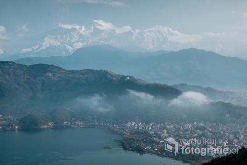 Zdjecie wykonane o poranku z niedalekiego szczytu obok jeziora, oferującego widok na Pokharę oraz Himalaje