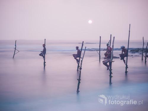 Zdjęcie zostało zrobione na Sri Lance i przedstawia rybaków łowiących ryby w tradycyjny sposób.