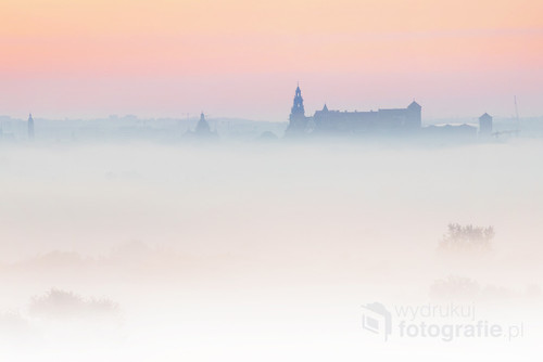 Fotografia przedstawia Wzgórze Wawelskie widziane z odległości 8 km wczesnym rankiem.