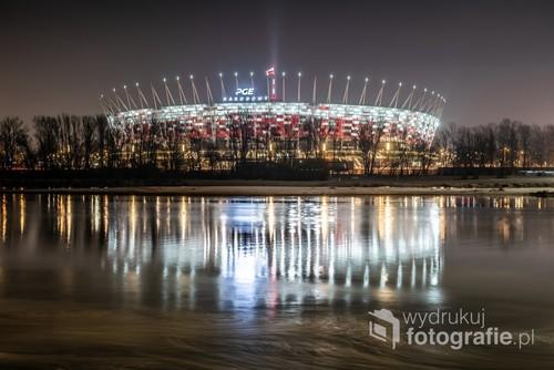 PGE Narodowy oświetlony w nocy i odbijający się w wodach Wisły