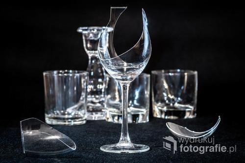 Potłuczony kieliszek do wina na tle pustych szklanych naczyń