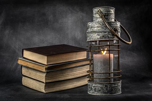 Stos książek z latarnią. Martwa natura. Symbol wiedzy i oświecenia