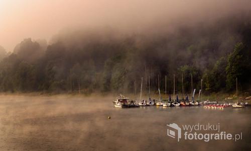 Przystań jachtowa na Jeziorze Żywieckim, wcześnie rano, początek jesieni. Ze względu na położenie w kotlinie górskiej jezioro często przykrywają poranne mgły, stopniowo podnoszone i rozwiewane przez wiatr.