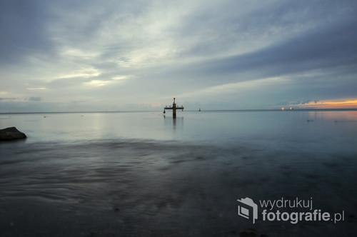 Zdjęcie przedstawia okolice mola w Gdyni Orłowie. Przed świtem spotyka się tam niewiele osób, a czasem jestem całkiem sama na plaży. Najlepszym czasem dla mnie jest kilka minut przed wschodem słońca, gdy mrok nocy walczy ze światłem dnia.