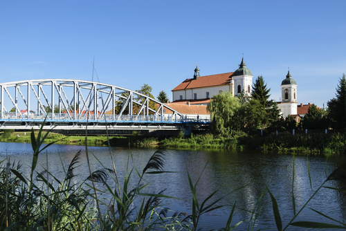 Kościół pw. Trójcy Przenajświętrzej w Tykocinie widziany zza rzeki Narew. Most przez rzekę pochodzi z Ziem Zachodnich. Kościół typu bazylikowego w stylu późnobarokowym.
