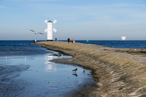 Stawa Młyny w Świnoujściu jest znakiem nawigacyjnym zbudowanym w XIX w. Stoi na końcu falochronu przy wejściu do portu. W oddali widać zbliżający się prom pasażerski.