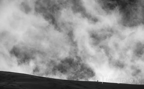 Fotografia przedstawia skialpinistę podążającego z Kasprowego Wierchu w stronę przełęczy Liliowe. W okresie w którym zostało wykonane zdjęcie występowały w Tatrach bardzo silne wiatry wzbijające w powietrze pył śnieżny widoczny w tle.