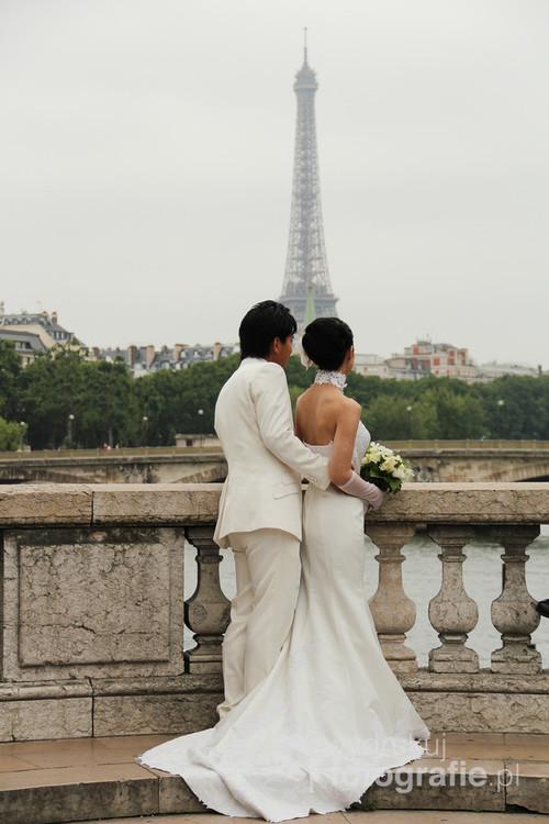 Fotografia została zrobiona podczas sesji ślubnej na moście Aleksandra III w Paryżu skąd rozpościera się wspaniały widok na Wieżę Eiffla i Sekwanę.