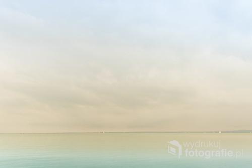 Jezioro Balaton nie bez przyczyny nazywane jest węgierskim morzem. Wieje tam porządny wiatr, co przyciąga miłośników żeglarstwa. I fotografów.  Oto kojący obraz horyzontu z majaczącymi żaglówkami. Wersja minimalistyczna w pastelowych kolorach.