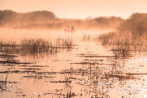 Rzeka Biebrza urzeka wiosną o wschodzie słońca, gdy mgła się podnosi, a z niej wyłania się postać wędkarza na łódce.