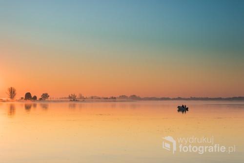Wschód słońca nad rzeką gwarantuje niezapomnianą feerię barw. Wędkarz na łodzi dopełnia piękny obraz.