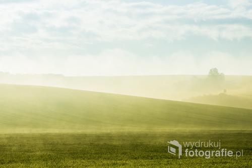 Wzgórza na Morawach w porannej mgle pod niebieskim niebem. Piękny i delikatny obraz, który przynosi ukojenie i spokój.