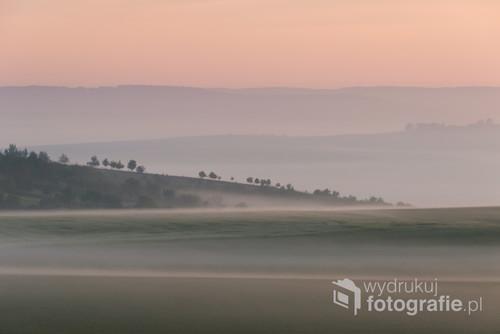 Tuż przed wschodem słońca otulone mgłą i porośnięte drzewami wzgórza na Morawach.