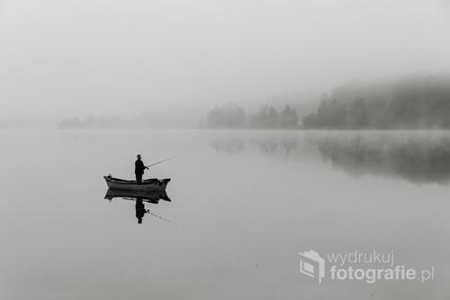 Wędkarz na  łódce, a za nim brzeg jeziora we mgle. Wstałam wcześnie, by utrwalić wschód słońca, które tego dnia spało dłużej niż ja i wędkarz.
