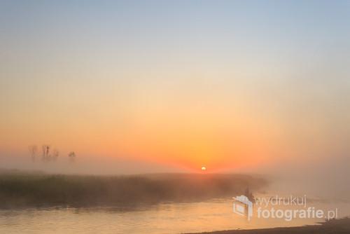Wschód słońca we mgle i wędkarz płynący po Biebrzy.