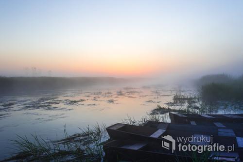 Wschód słońca we mgle tworzy tajemniczą atmosferę. Łodzie zacumowane na brzegu rzeki pokazują, że nie jest to miejsce odludne.