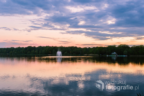 Zachód słońca nad jeziorem, w którym odbija się niebo i drzewa na brzegu. Zaskakuje tylko fontanna na środku.