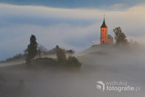 Zdjęcie wykonane w Słowenii,  przedstawia koścół w porannej mgle.
