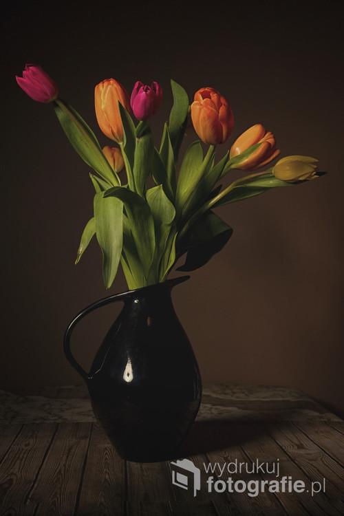 Zdjęcie przedstawia kwitnące tulipany w wazonie jako martwa natura.