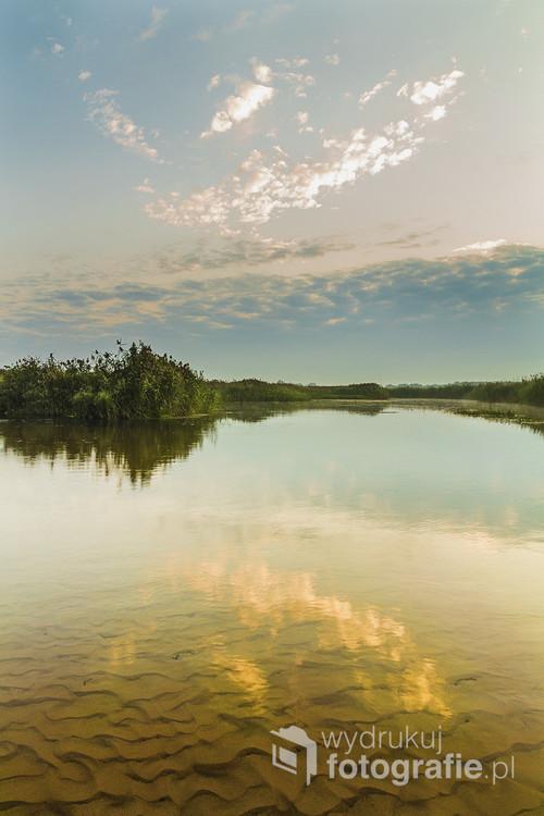 Odbicie nieba w tafli wody rzeki Biebrzy, jesienią.