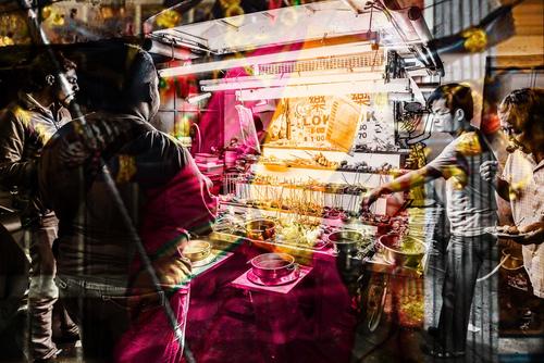 Stoisko z jedzeniem ulicznym w mieście George Town w stanie Penang w Malezji. Zdjęcie wykonane techniką podwójnej ekspozycji.