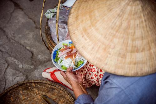 Sprzedawczyni warzyw na przenośnym straganie ulicznym, jedząca lunch. Hue, Wietnam.