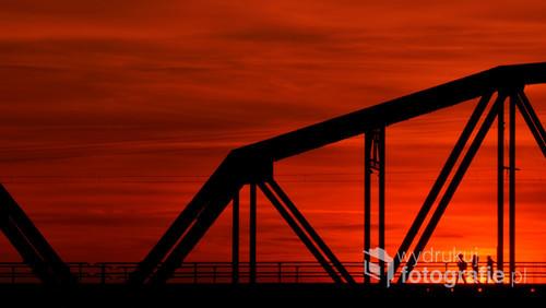Fotografia wykonana w listopadzie o zachodzie słońca. Most kolejowy w Warce na rzece Pilica. Chwilę po przejeździe pociągu pojawiła się na nim grupa ludzi...