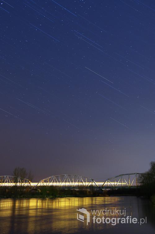 Fotografia złożona z dwóch ekspozycji jednego kadru, 30 minutowej i 15 sekundowej. Przedstawia nocny pociąg przejeżdżający przez kolejowy most na rzece Pilicy w Warce.