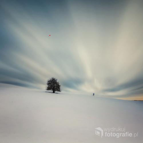Zimowy surrealistyczny pejzaż z człowiekiem puszczającym latawiec.