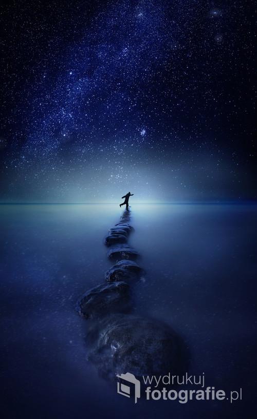 Noc,gwieździste niebo, falochron i niebezpieczne zabawy z wykorzystaniem równowagi. Surrealistyczny pejzaż, fotowizja.