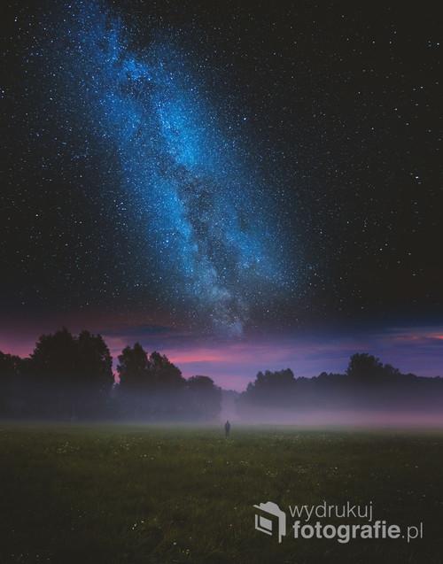 Dzika łąka, mgła, noc, człowiek i niebo. Surrealistyczna fotowizja.