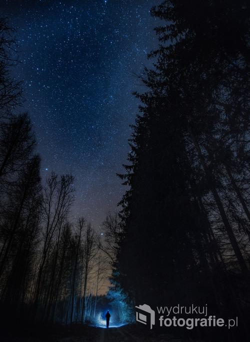 Nocny pejzaż, człowiek z latarką i ciemna noc.