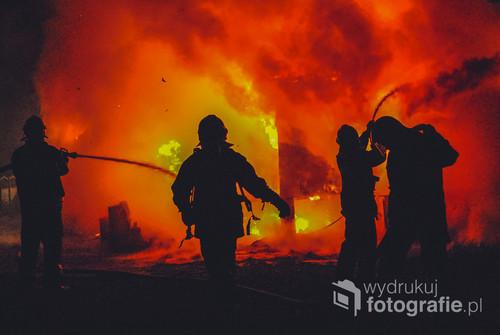 Fotografia ta przedstawia strażaków walczących z pożarem budynku mieszkalnego zwanego