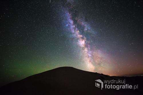 Tuż po zachodzie słońca, nad śpiewającą wydmę w parku narodowym Altyn-Emel w Kazachstanie, wzeszła Droga Mleczna. Gwiazdy na pustyni świecą niesamowitym blaskiem, nieprzytłumione innymi źródłami światła. Zielona łuna po lewej stronie to poświata ziemskiej atmosfery, widoczna tylko pod najciemniejszym niebem.