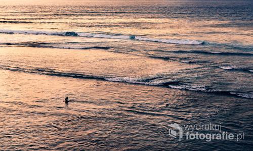 Surfer o zachodzie słońca na plaży Uluwatu. Bali, Indonezja 2016.