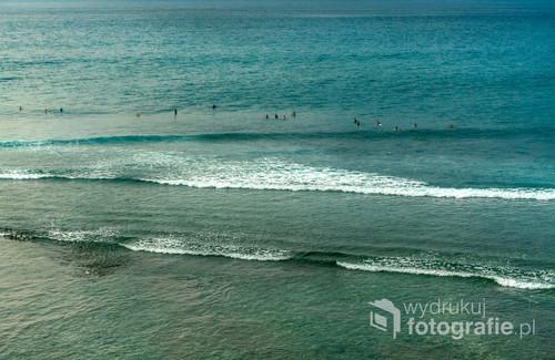 Surferzy czekający na falę przy słynnej plaży Uluwatu. Bali, Indonezja 2016.
