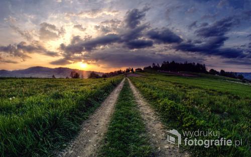 Fotografia wykonana w miejscowości Juszczyn, na południu Polski, przedstawia ostatnie promienie słońca wydzierające się spod warstwy chmur, by ostatni raz oświetlić drogę i pola uprawwne