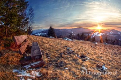 Pierwszy wiosenny kadr 2017 roku, wykonany w Zawoi Przysłop. Słońce chowające się za góry oświetla samotną, pustą ławkę.