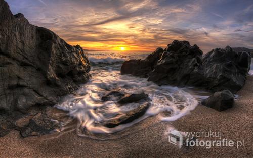 Zdjęcie zachodzącego słońca na plaży Olmeto, Korsyka, aparat ulokowany w szczelinie między 2 skałami, do której wdziera się wzburzon morze.
