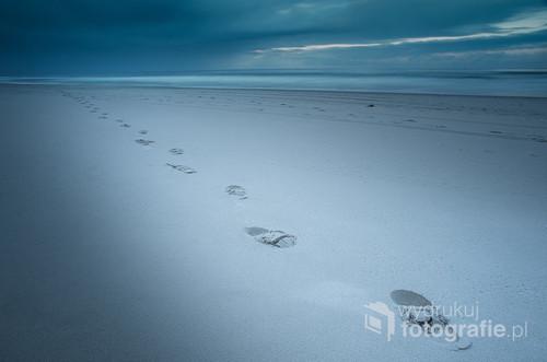 Ślady butów na piasku przyciągnęły moją uwagę. Wydają się znikać na linii horyzontu.