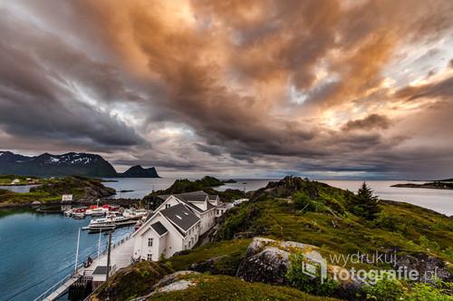 Fotografia przedstawia zachód słońca nad XIX wiecznym starym portem przekształconym obecnie w  Hotel w północnej Norwegii na wyspie Senja