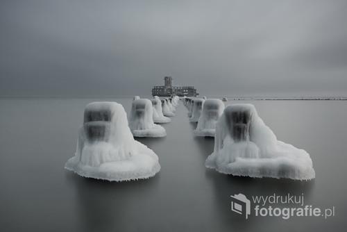 Zdjęcie zostało wykonane nad Morzem  Bałtyckim w miejscowości Babie Doły.Przedstawia historyczne miejsce a mianowicie torpedownię z czasów II wojny światowej.Zastosowano technikę długiego naświetlania w celu rozmycia wody oraz nieba.Drewniane paliki w czasie zimy obfitującej w niską temperaturę pokryły się czapami lodowymi,które dodają uroku temu miejscu.