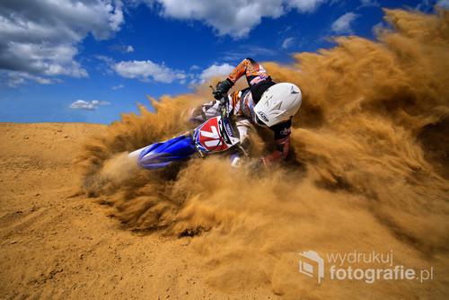 Fotografia została wykonana na torze motocrossowym w Kwidzynie.Zawodnik podczas pokonywania piaszczystego zakrętu, uchwycony przeze mnie obiektywem szerokokątnym.Najlepsze z najlepszych 5/2014 w kategorii sport w Foto Kurier oraz pierwsze miejsce w konkursie Zdjęcie miesiąca 5/2014