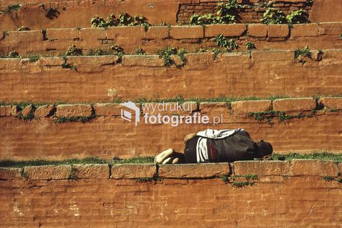 Mieszkaniec stolicy Nepalu śpi na schodach świątyni w centralnej części miasta. Durbar Square, Kathmandu, Nepal.  1995 rok. fotografia analogowa/diapozytyw.