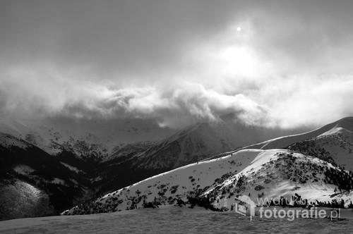 Widok z popularnego Grzesia w Tatrach Zachodnich. Przed chwilą tu dotarliśmy, przed chwilą widać było jeszcze całą panoramę. Nic nie zapowiadało, że za kilka minut góry połknie mleczna substancja. Udaje się zrobić jeszcze tylko kilka zdjęć- na ostatnim panuje niepodzielnie biel mgły i niesionego wiatrem śniegu, widać jedynie Sylwię w czerwonej kurtce z zaciągniętym kapturem i drogowskaz.  Załamanie pogody. Zaraz wracamy do schroniska na Polanie Chochołowskiej. Zdjęcie zostało wykonane 29 grudnia 2011r.
