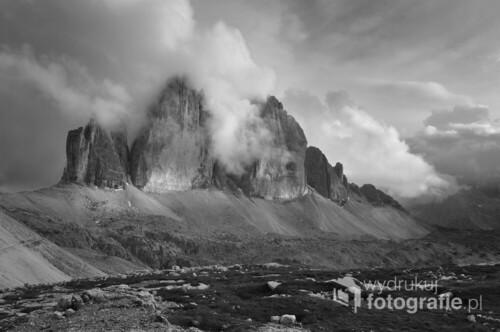 """Zdjęcie przedstawia słynne szczyty Tre Cime di Lavaredo we Włoskich Dolomitach (podgrupa Dolomiti di Sesto). Najwyższy spośród tych sklalnych klocy przekracza wysokość 600m licząc od podnóża ściany do szczytu (2999m.n.p.m). Zdjęcie wykonane z okolic schroniska Rifugio Antonio Locatelli (Dreizinnenhütte, 2450m.n.p.m.). Zdjęcie prezentowane było na wystawie pokonkursowej XXXVII Międzynarodowego Konkursu Fotograficznego im. Jana Sunderlanda """"Krajobraz Górski"""" organizowanego przez Miejski Ośrodek Kultury w Nowym Targu."""