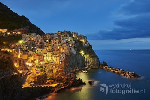 Fotografia przedstawia popularne  oświetlone miasteczko nocą, położone nad morzem liguryjskim we Włoszech.